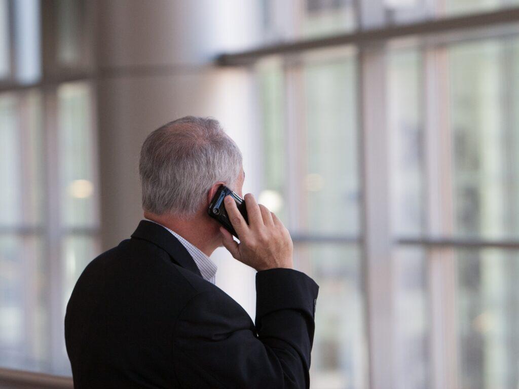 Et billede af en mand der taler i telefon mens han kigger ud af vinduet